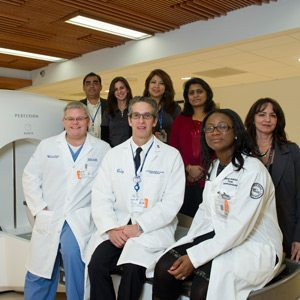 Members of the Radiation Medicine team showcase the GammaKnife at the new facility at Center for Advanced Medicine.  Front row, l-r:  Brett Cox, MD chief of brachytherapy; Louise Potters, MD, chair of radiation medicine, Kerry-Ann Brown, RN; back row, l-r:  Sherin Jospeh, chief radiation therapist, RTT, Nikoleta Levendis, RTT, Grace Ouellette, RTT, Rani Paul, RTT, and Dawn Carillo, RTT.