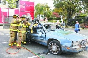 Firefighters demonstrated vehicle extrication, which sometimes involves removing the front window using a battery-operated cutter or removing the doors and roof using hydraulic tools.