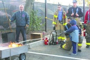 Alert Chief James Neubert oversaw a demonstration on how to use a fire extinguisher on a trash fire.
