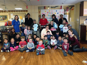 Residents of Grace Plaza with children and staff of Clasp Day Care Center at their annual holiday celebration