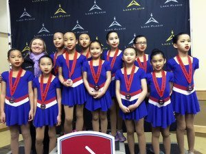 Coach Erica Beggs (back row, left) stands with her Ice Gems silver medalists.