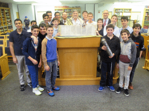 Over the past 15 years, more than 250 students at the academy have been instructed by Dr. Paul Brody, pictured wearing tallit (a prayer shawl), along with Middle School Principal Rabbi Adam Acobas and Head of School Rabbi Jeffrey Kobrin, who is surrounded by the students.