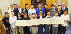 From left: Dr. Paul Brody (back row, third from left), holding the Megillah case, is pictured with Rabbi Adam Acobas, Rabbi Jeffrey Kobrin and the students.