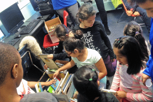 CLASP children eagerly look through books donated by GNTA.
