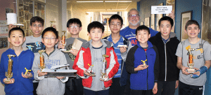 Maglev Club members proudly hold their winning trophies and vehicles, from left: John Xie, Neal Sodhi, Collin Li, Stephen Ye, Jansen Wong, Andrew Dea, Advisor Randy Lane, Robert Gan, Kobe Zheng and Reid Fleishman.