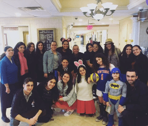 Elnaz Ramezani, volunteer; David Sterling, assistant director of Therapeutic Recreation; community members; and children celebrate Purim.