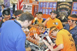 Members of Team Rebellion make adjustments to their robot.