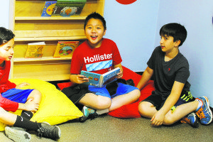Some of the students get comfortable in the reading area.