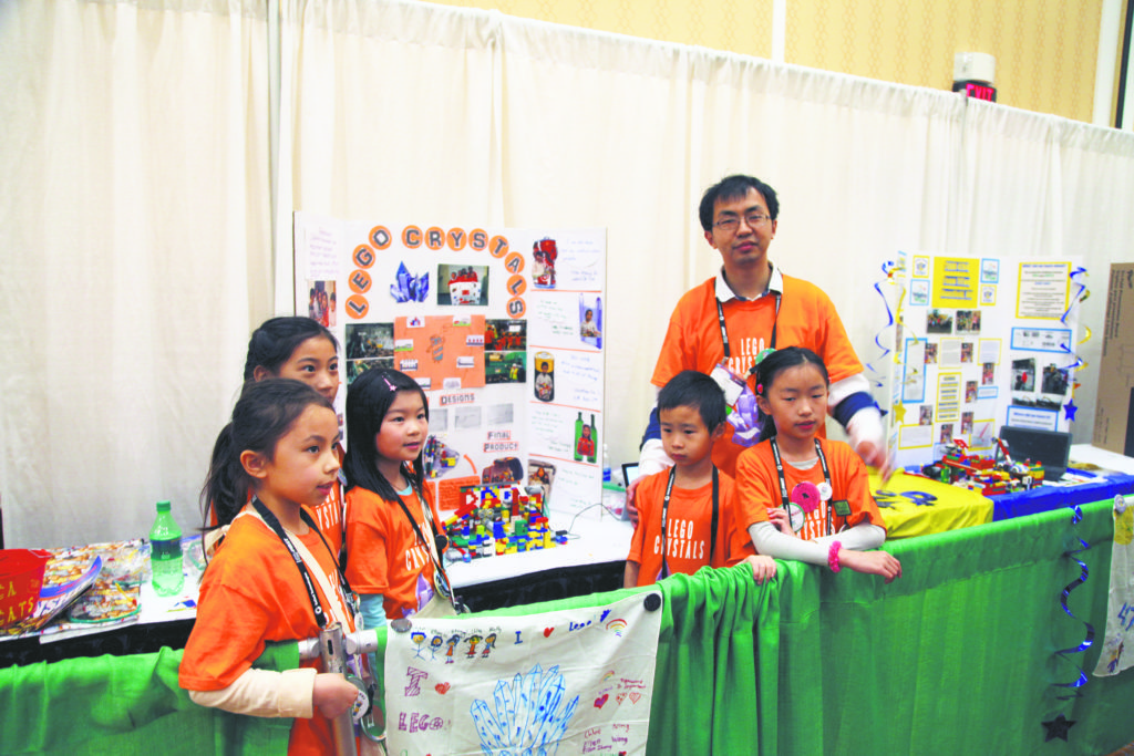 Team Lego Crystals' at the booth (from left): Holly Krause, Ellen Zhang, Ellen Wang, Mofan Yu, Chloe Ning and Head Coach Feng Ning