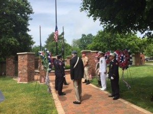 Military service representatives put wreaths at the Wall of Remembrance on the Village Green. They represent those lost since WW I in GN. Parade Marshal Rear Admiral James Helis is in white at right.