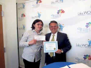 Ryan Harvey, a ninth grader at The Village School, is presented with a $3,000 check and first place certificate for his essay by Peter Klein, president of The Claire Friedlander Family Foundation.