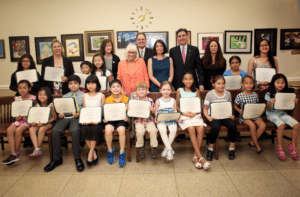 Councilwoman Lee Seeman, Town Supervisor Judi Bosworth, Receiver of Taxes Charles Berman, Councilwoman Dina De Giorgio, Town Clerk Wayne Wink and GCAC Associate Director Caroline Sorokoff are with student artists from the Gold Coast Arts Center.