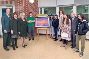 Grouped around the poster from SEAL students are (from left): Board Vice President Lawrence Gross; Board Trustee Susan Healy; Board President Barbara Berkowitz; SEAL students Scott Stich, Serena Chen and Jordan Swope; Board Trustee Monique Bloom; VS student Phoebe Miller; Board Trustee Donald Ashkenase; and VS student Sabrina Geffner. (Photo by Jeff Barlowe)