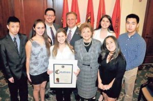 PSA Contest winners (from left, front row): Richard Lau, Francesca De Shadow and Haley Raphael, contest judge Linda Mangano, and Hailey Rich; (back row): TV/film teacher Robert Zahn, County Executive Ed Mangano, Nicole Marinescu and Michael Shen