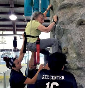 Rec aide Dana Giannone spots Sylvia Tankel as she makes her way up the rock wall.