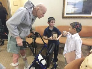 First-grade students visit a senior at the Atria.