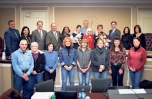 From left, back row: Public Safety Commissioner Andrew DeMartin, Councilwoman Anna Kaplan, Receiver of Taxes Charles Berman, Councilwoman Viviana Russell, Shelter Director Jenna Givargidze with a Maltese named Benji, Dr. Bob Slifkin, Supervisor Judi Bosworth, Susan Hassett with a Beagle named Keeper, Town Clerk Wayne Wink, Councilwoman Dina De Giorgio, Councilwoman Lee Seeman; front row (not from left):  John Luca, Ruth Stern, Linda Tyras, Paula Kellner, Roseanne Wellmaker, Marianne Sikora, Denise Waters and Kim Lasek