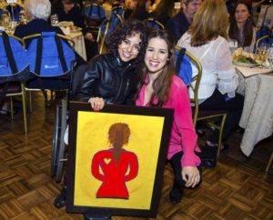 Mariah, a senior at Henry Viscardi School at The Viscardi Center, presenting the painting of Chilina she created, with Chilina
