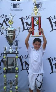 Jordan Reznik proudly displays his trophy from the Little Mo International tournament in Forest Hills.