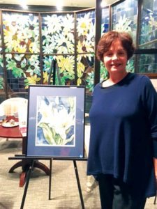"Nina Wolf stands next to ""Lillies,"" one of her two watercolors included in The Natural World exhibition on view in Glen Cove through Nov. 10."