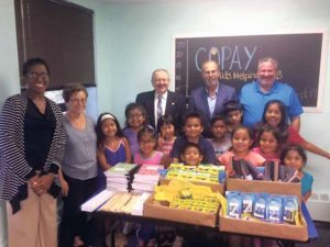 Ruth Trujillo-Pertew, LCSW, assistant to Executive Director of COPAY Ron Swartz; current President of the Rotary Club of Great Neck Roger Chizever; current Vice President Lidia Epel and Leonard N. Katz, Rotary Club of Great Neck immediate past president, with grateful children excited about the school supplies