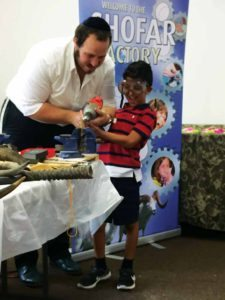 A child learns how to use a drill while making a shofar.