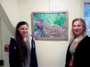 "Great Neck North High senior Malka Lohmann poses in front of her mixed-media self-portrait ""Good Hair Day"" with her mother Dina Miller."
