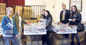 Rebecca Gilliar (second from left) helps residents at the Book Giveaway as former North Hempstead Town Supervisor Jon Kaiman (second from right) finds some books to take home.