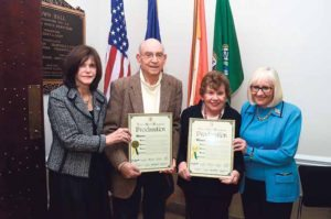 The couple was presented with proclamations by Bosworth (right) and Councilwoman Lee Seeman (left) before the board meeting at Town Hall in Manhasset.