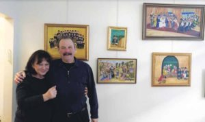 Owners Avital and Peter Kornblum stand next to their collection of artist Adina Gross's Israeli folk paintings, many of which depict biblical scenes.