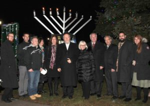 Local officials pose in front of the menorah.