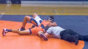 South Senior Captain Nick Belitsis (top) pins down North sophomore Ariel Arabian as the referee confirms victory for South.