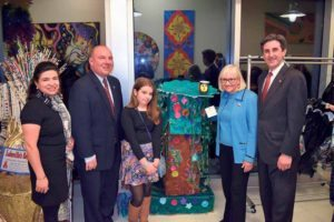 "From left: North Hempstead Councilwoman Anna Kaplan, Councilman Peter Zuckerman, Willets Road School student Alyson Zeller, Supervisor Judi Bosworth and Town Clerk Wayne Wink pose with Zeller's submission, ""Recycled Paradise."""